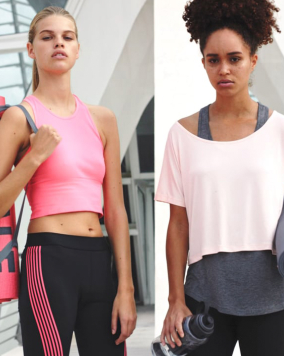Two woman holding yoga mats and wearing workout clothes