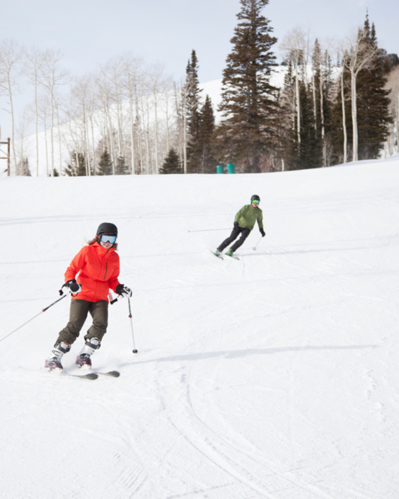Two people skiing down mountains