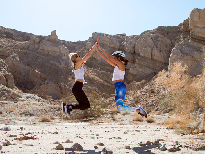 Two woman jumping and high-fiving in the Palm Spring desert, during CBC FIT House