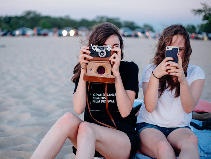 Two female Gen Z teenagers take photos