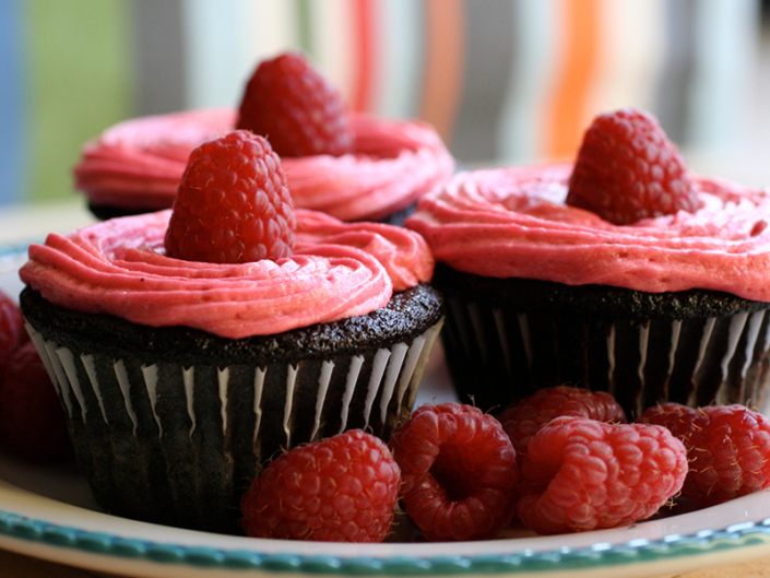 Red frosted chocolate cupcakes with raspberries