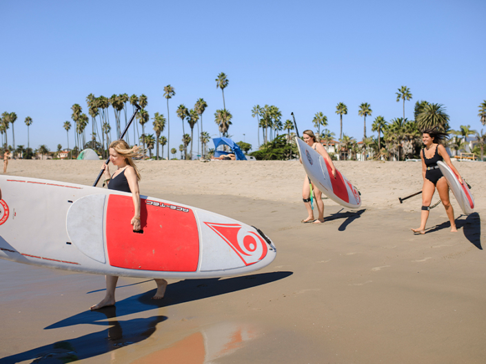 Group of women on beach with paddleboards