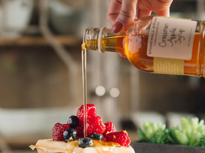 Person pouring Stonewall Kitchen syrup onto a stack of pancakes