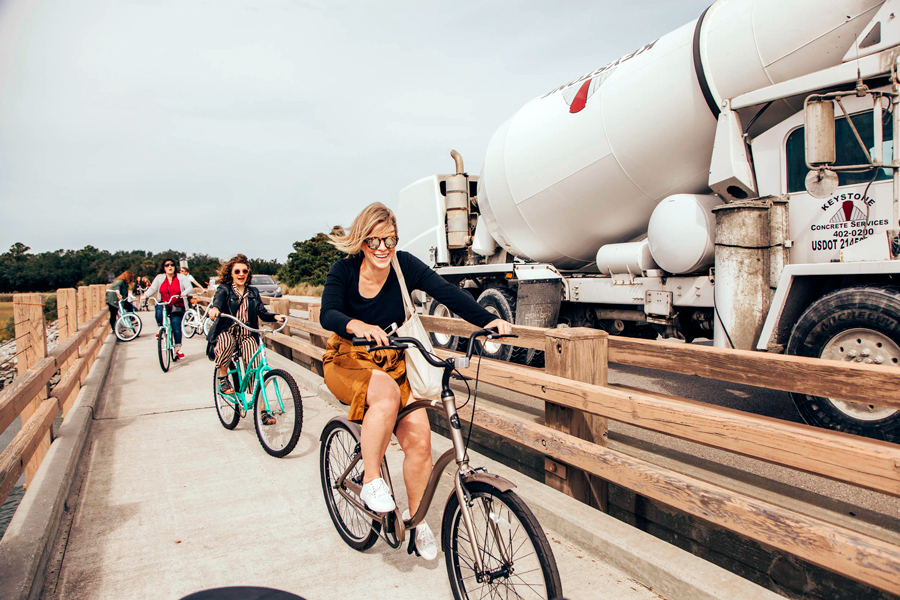 Influencers and press riding bikes on a beach dock at the Charleston Experience
