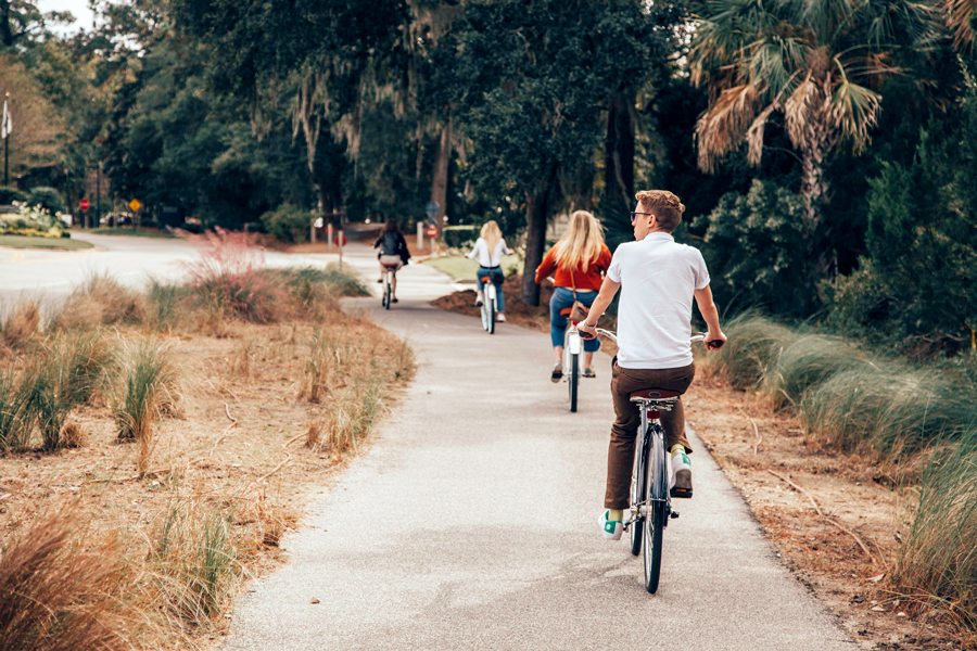 Influencers riding bikes on the sidewalk at the Charleston Experience
