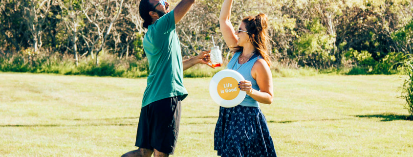 Man and woman holding frisbee giving a high five