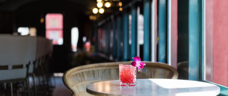 pink cocktail with flower garnish