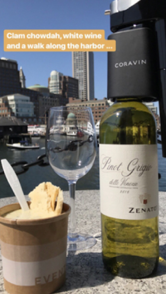 A Coravin, clam chowder, and white wine placed on a rock at the Boston Harbor