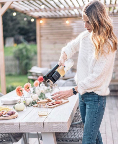 Influencer using a Coravin system to pour a glass of wine