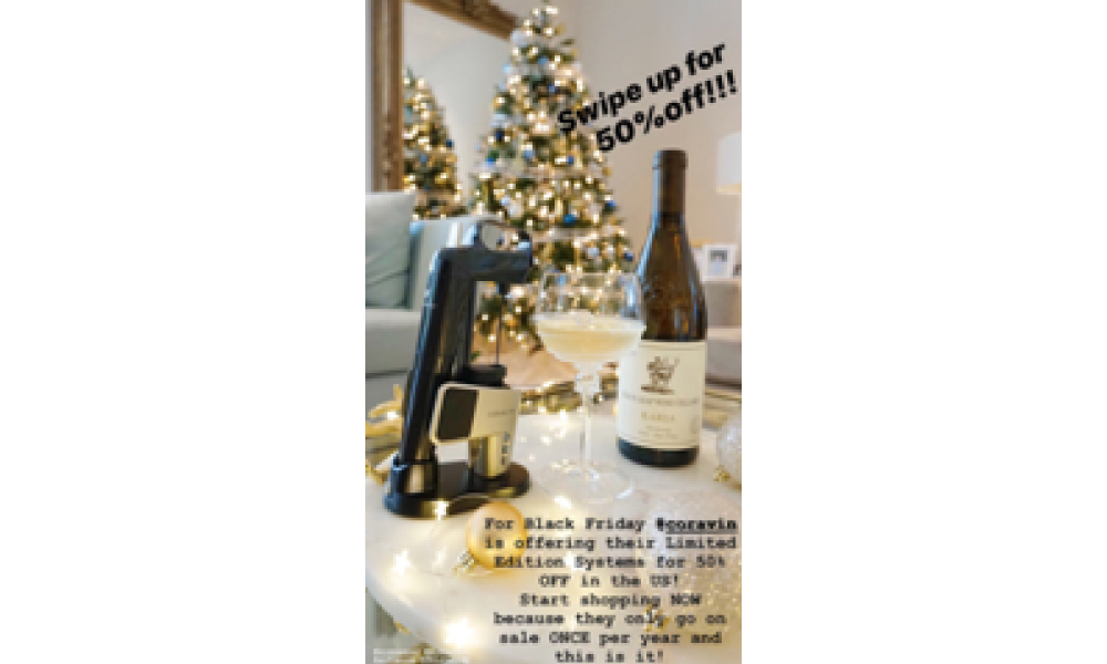 Coravin system next to a glass of wine in front of a Christmas Tree