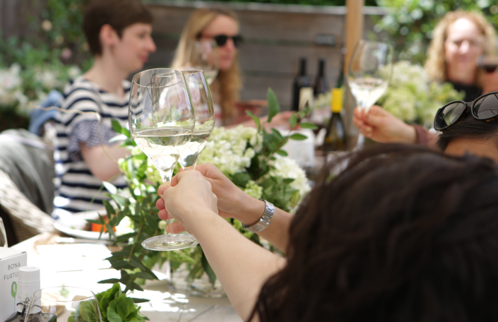Influencers and press toasting white wine outside at a pinic table