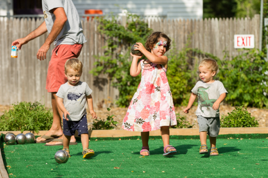 Three children playing in a yard at a Garnet Hill experiential program