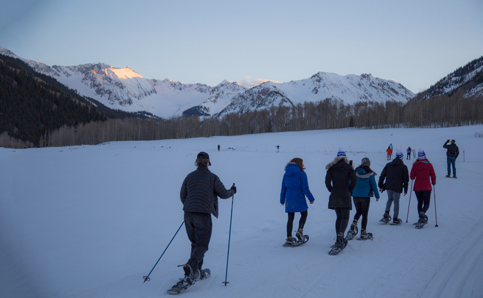 Group of influencers and press snowshoeing through the Aspen mountains