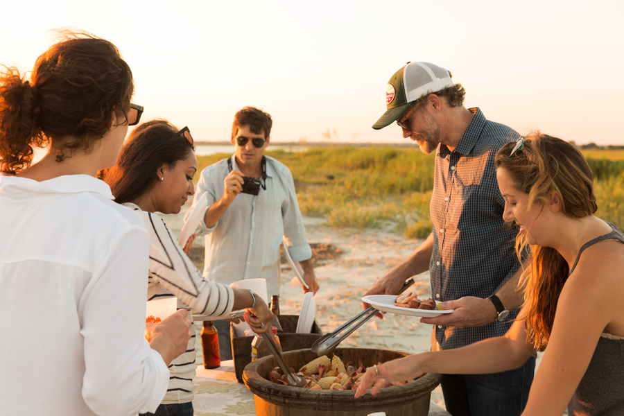 Influencers and press on the beach at a shrimp boil at the Charleston Experience