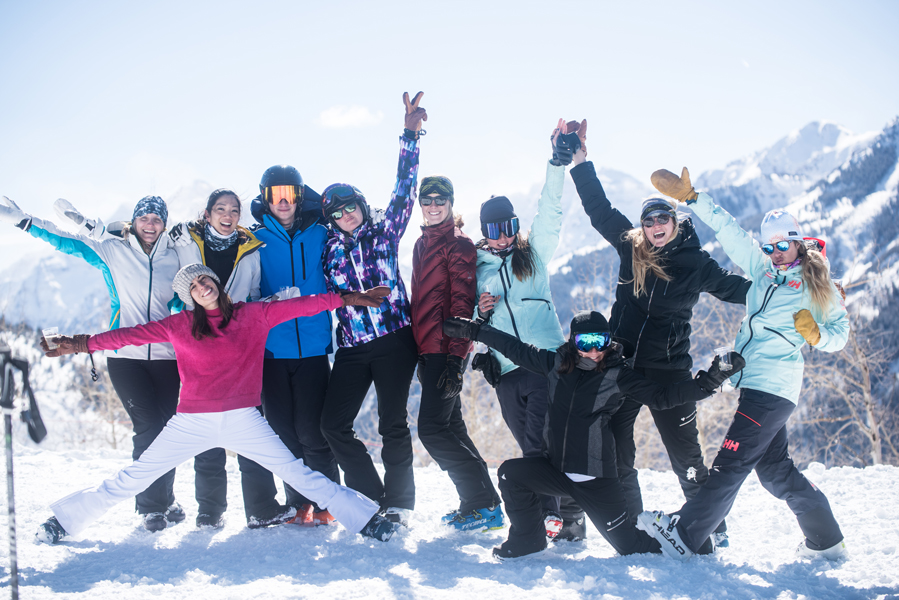 Group of influencers and press posing at the top of a snowy mountaint