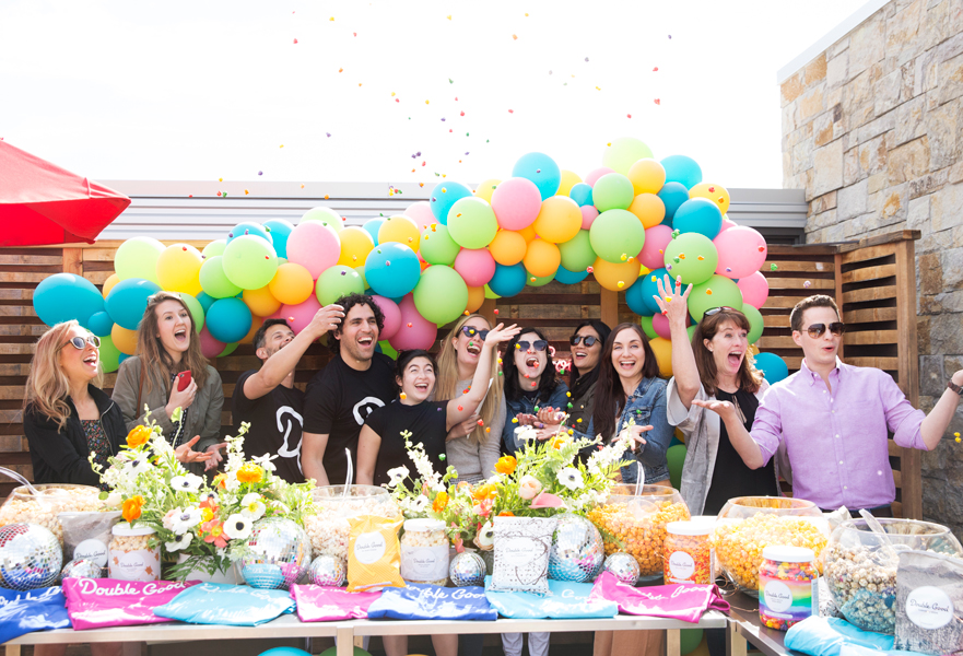 Influencers and editors throwing confetti in front of a popcorn bar at Culinary House