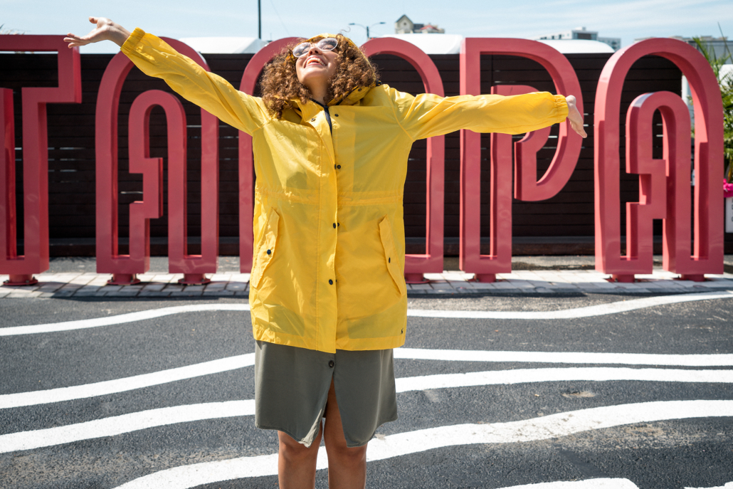 Woman in raincoat in front of Tampa signage