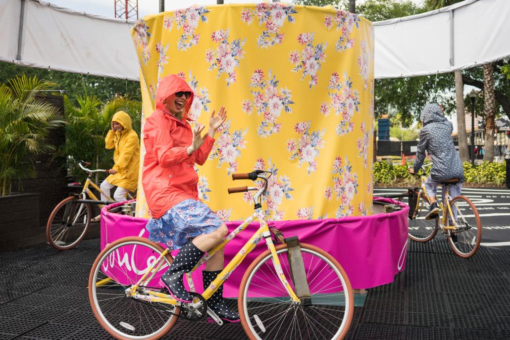 Women in raincoats riding bike carousel