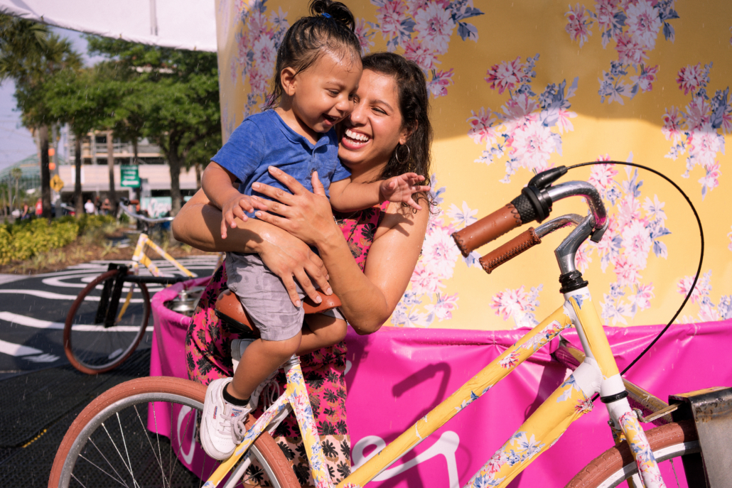Mother and daughter laughing on bike carousel