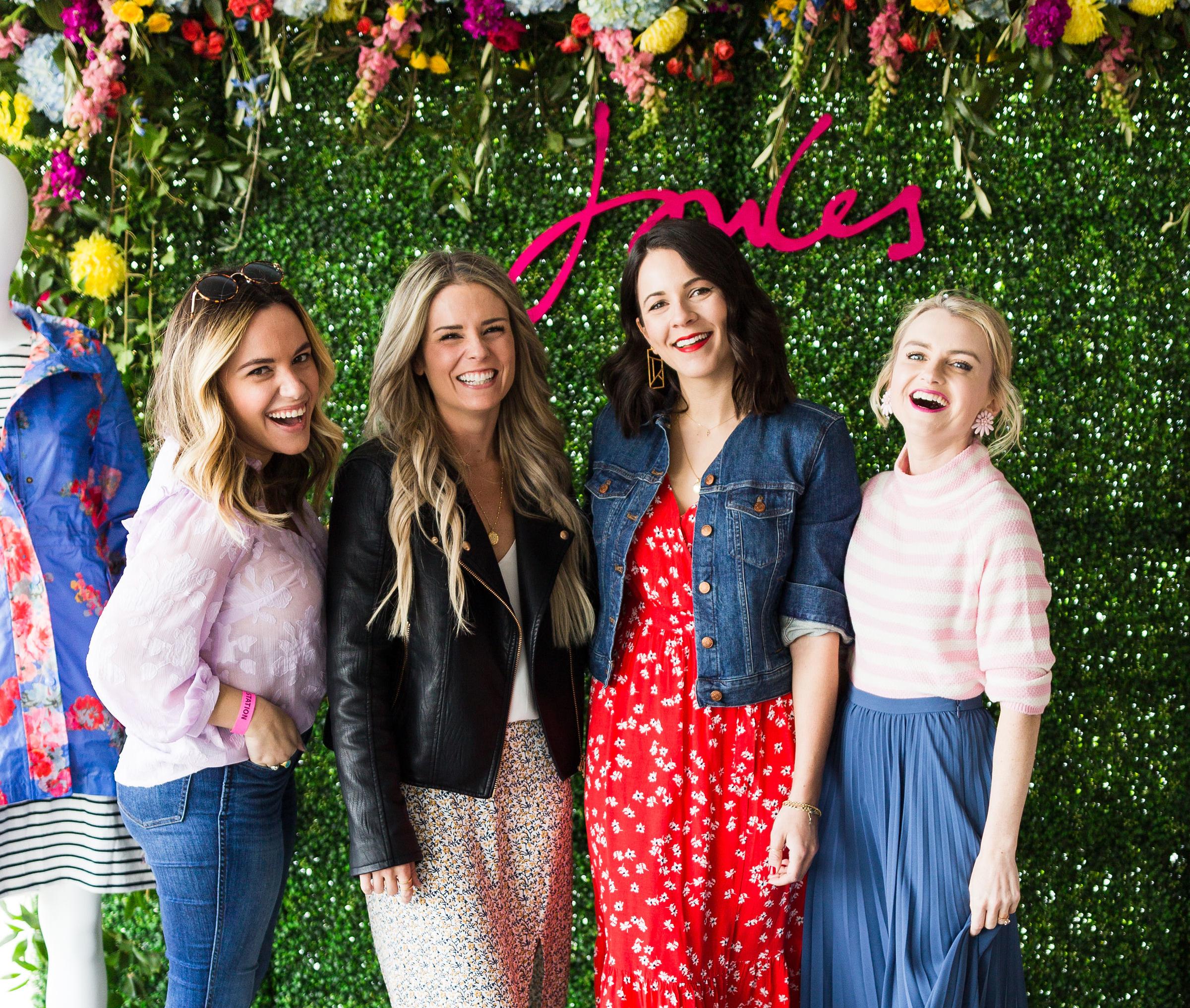 Women posing in from of flower wall