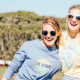 Two women wearing Life Is Good t-shirt holding each other in sunlight