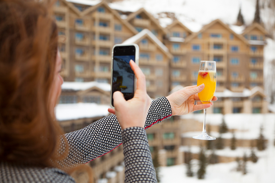 Influencer taking a picture of drink with mountain background at Deer Valley Experience