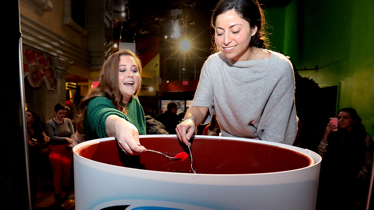 Couple women dipping spoons into Ocean Spray's world's largest can of cranberry sauce