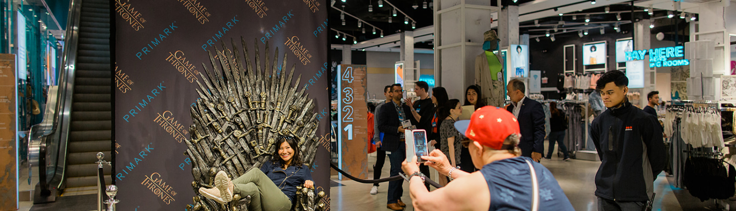 Fans in costume pose on the Iron Throne at Primark
