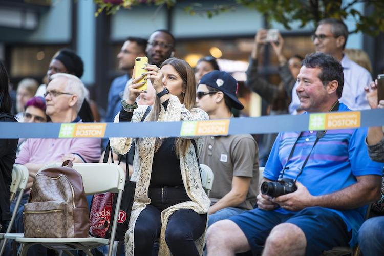 An audience member takes a video of the fashion show