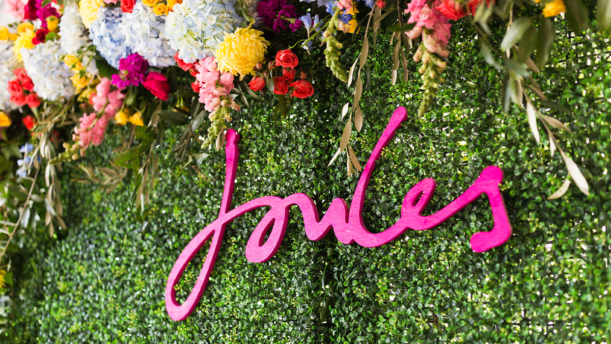 Joules Right As Rain event name on floral wall