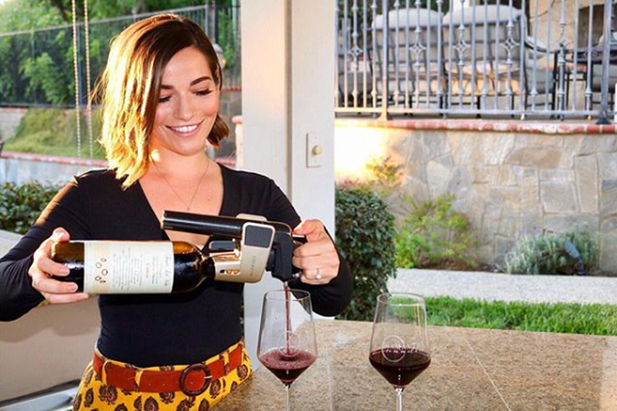 Influencer pouring wine using a Coravin outside