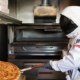 Man in astronaut suit taking pizza out of oven