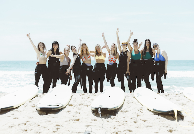 Media and influencers wearing SwimUSA suits and wetsuits with surfboards in front of ocean
