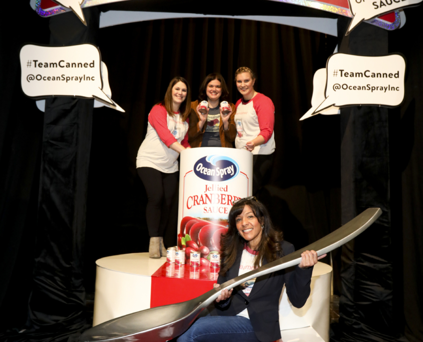 Women posing around Ocean Spray's world's largest can of cranberry sauce