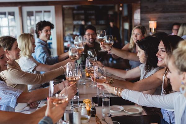 Media and influencers cheers-ing at Vineyard Vines dinner
