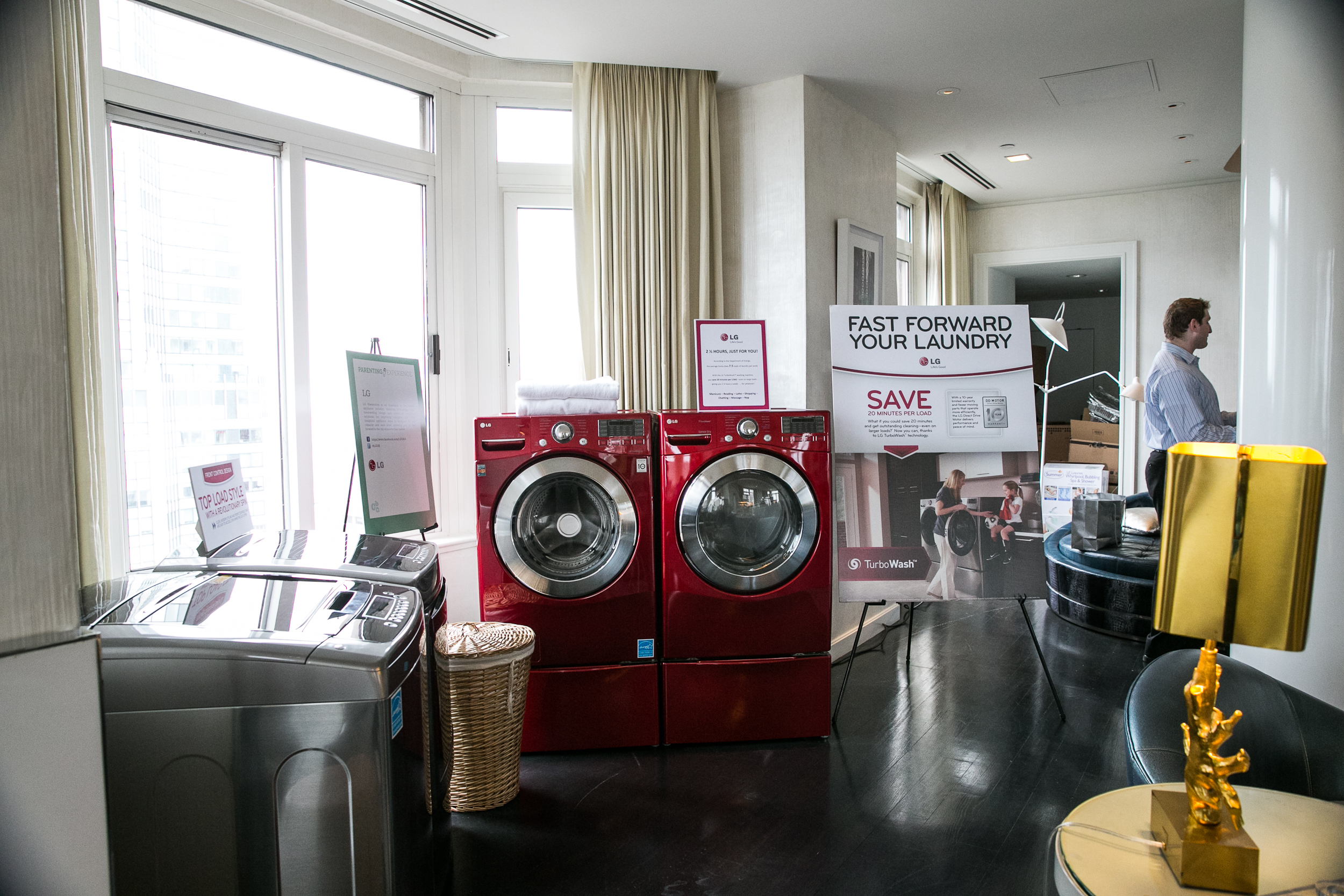 """display of washing machine and dryer with poster saying """"fast forward your laundry"""" at cbc parenting house"""