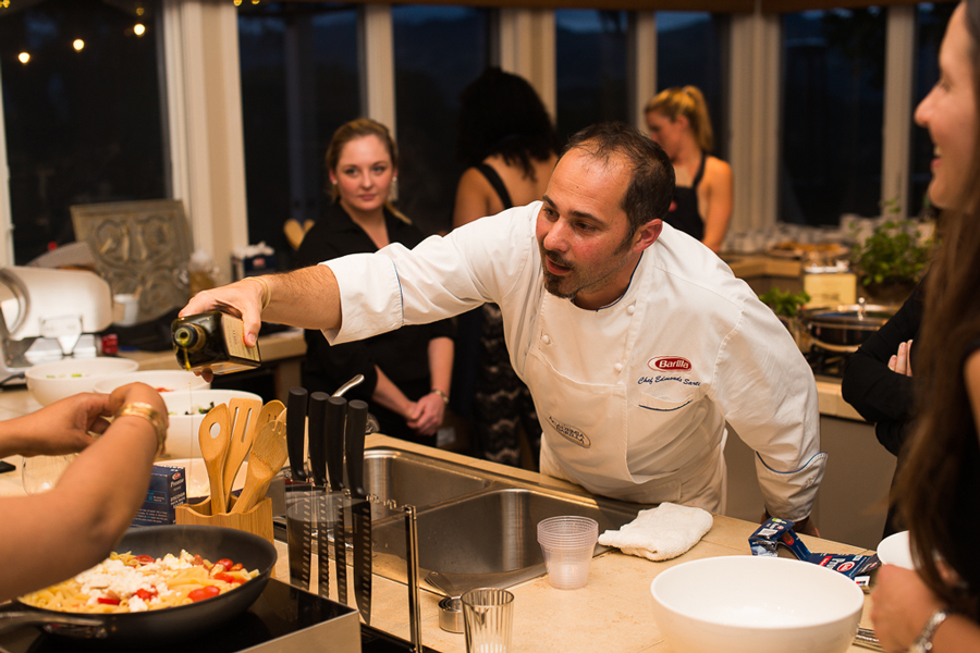 Barilla chef pouring olive oil into pasta dish at Culinary House
