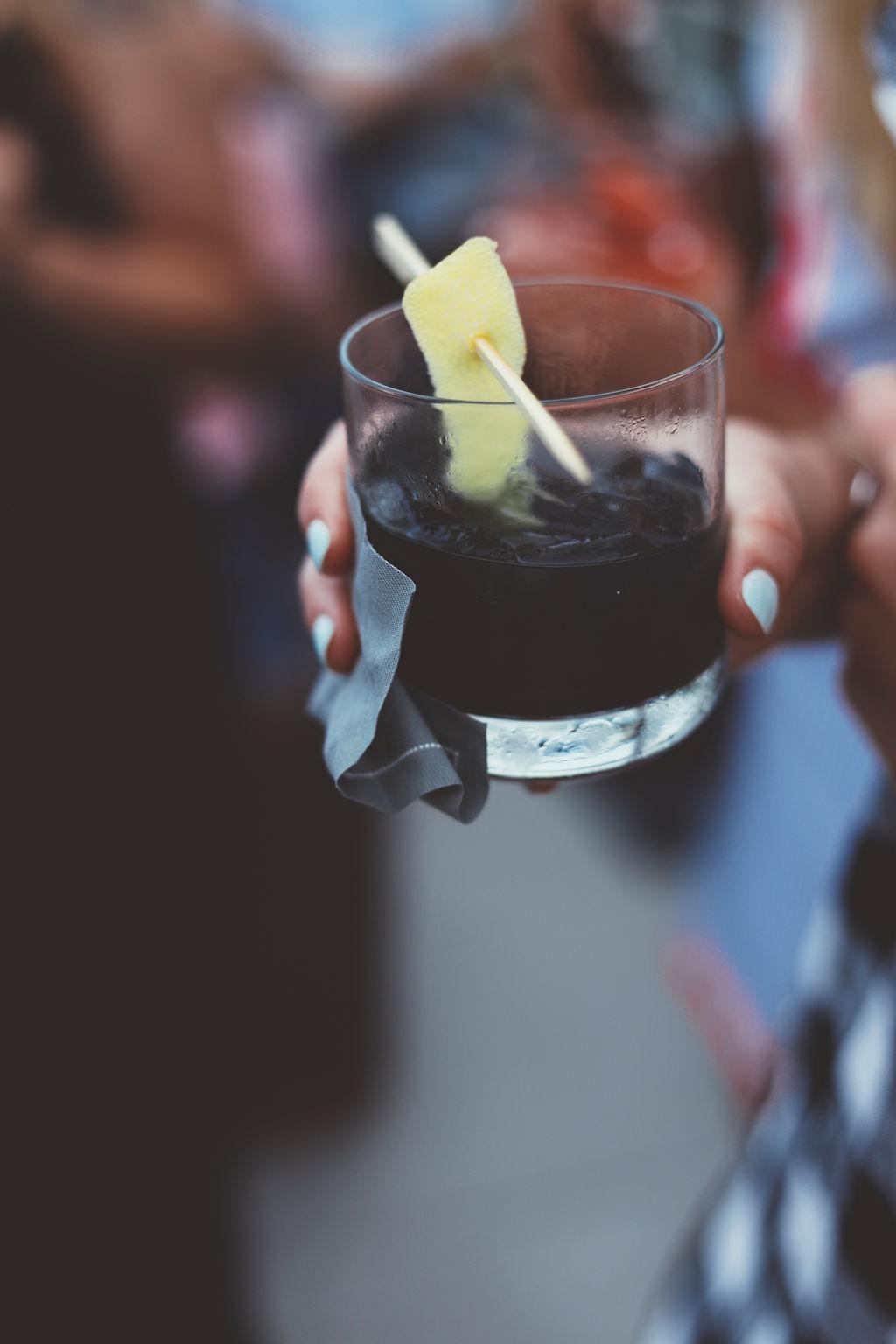 Dark cocktail in hand