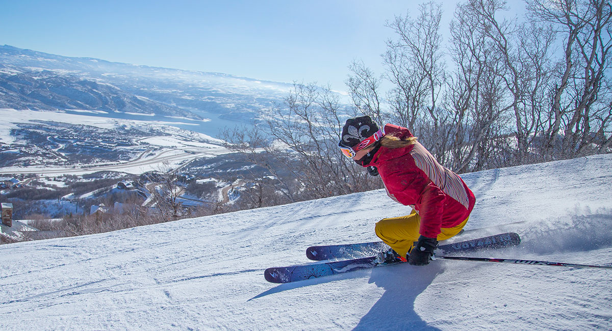 woman in red jacket skiing down mountain at CBC Deer Valley